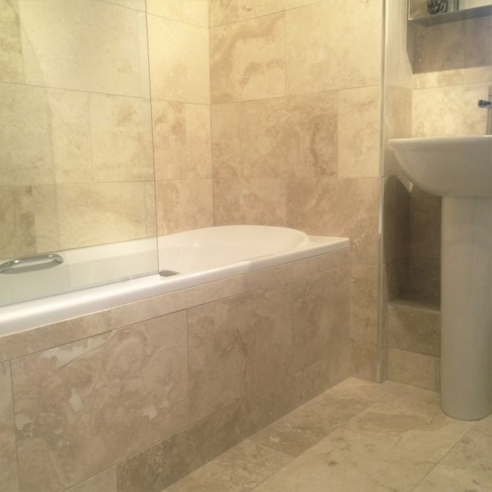 A bathroom with travertine tiles