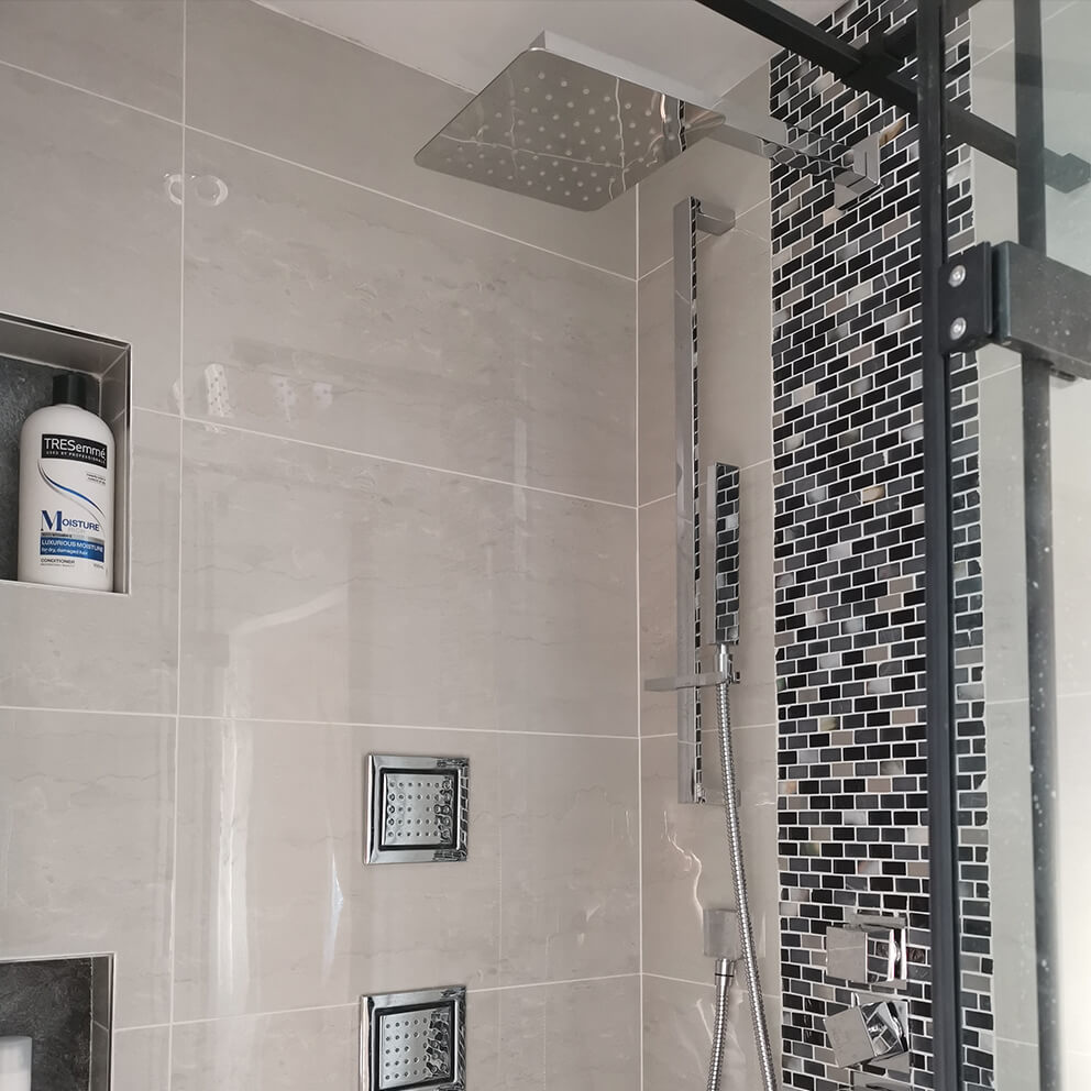 A shower head with patterned metallic brick mosaic tiles surrounding it